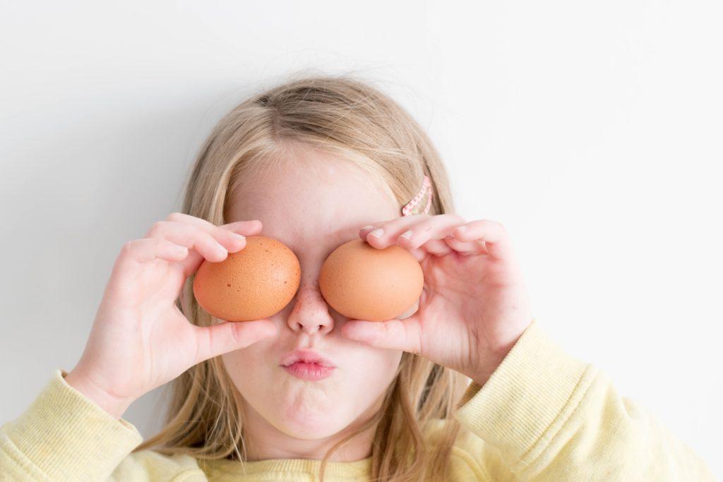 girl holding eggs on her eyes